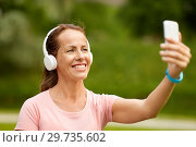 Купить «woman in phones takes selfie by smartphone at park», фото № 29735602, снято 15 июня 2018 г. (c) Syda Productions / Фотобанк Лори