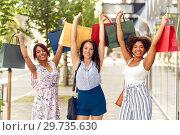 Купить «happy women with shopping bags on city street», фото № 29735630, снято 22 июля 2018 г. (c) Syda Productions / Фотобанк Лори