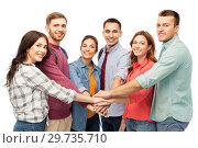Купить «group of smiling friends stacking hands», фото № 29735710, снято 10 ноября 2018 г. (c) Syda Productions / Фотобанк Лори