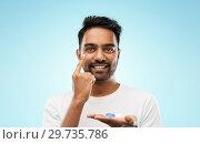 Купить «young indian man applying contact lenses», фото № 29735786, снято 27 октября 2018 г. (c) Syda Productions / Фотобанк Лори