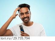 Купить «smiling indian man with trimmer touching his hair», фото № 29735794, снято 27 октября 2018 г. (c) Syda Productions / Фотобанк Лори