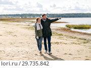 Купить «couple walking along autumn beach», фото № 29735842, снято 29 сентября 2018 г. (c) Syda Productions / Фотобанк Лори