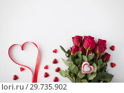 Купить «close up of red roses and heart shaped candies», фото № 29735902, снято 8 февраля 2018 г. (c) Syda Productions / Фотобанк Лори