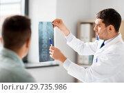 Купить «doctor showing x-ray to patient at hospital», фото № 29735986, снято 25 августа 2018 г. (c) Syda Productions / Фотобанк Лори