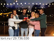 Купить «friends clinking party cups on rooftop at night», фото № 29736030, снято 2 сентября 2018 г. (c) Syda Productions / Фотобанк Лори