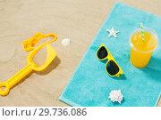 Купить «sunglasses, sand toys and juice on beach towel», фото № 29736086, снято 27 июня 2018 г. (c) Syda Productions / Фотобанк Лори