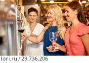 Купить «happy women pouring wine from dispenser at bar», фото № 29736206, снято 25 июня 2018 г. (c) Syda Productions / Фотобанк Лори
