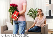Купить «woman looking at man with flowers and gift at home», фото № 29736282, снято 30 ноября 2018 г. (c) Syda Productions / Фотобанк Лори