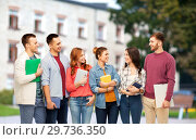 group of smiling students talking over campus. Стоковое фото, фотограф Syda Productions / Фотобанк Лори