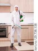 Купить «Professional contractor doing pest control at kitchen», фото № 29738138, снято 29 октября 2018 г. (c) Elnur / Фотобанк Лори