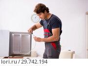 Купить «Young handsome contractor repairing fridge», фото № 29742194, снято 5 октября 2018 г. (c) Elnur / Фотобанк Лори