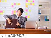 Купить «Young handsome employee working in the office», фото № 29742714, снято 16 октября 2018 г. (c) Elnur / Фотобанк Лори