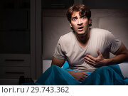 Купить «Young man scared in his bed having nightmares», фото № 29743362, снято 18 сентября 2018 г. (c) Elnur / Фотобанк Лори