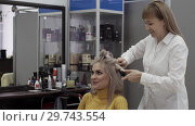 Купить «Positive Female Hairdresser Doing Hairstyle To Blonde Girl», видеоролик № 29743554, снято 20 мая 2019 г. (c) Pavel Biryukov / Фотобанк Лори