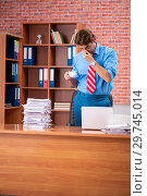 Купить «Young employee with excessive work sitting at the office», фото № 29745014, снято 29 августа 2018 г. (c) Elnur / Фотобанк Лори
