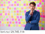 Купить «Young handsome man in conflicting priorities concept», фото № 29745114, снято 17 августа 2018 г. (c) Elnur / Фотобанк Лори