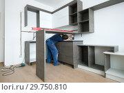 Купить «Установка кухонной мебели в новой малогабаритной квартире», фото № 29750810, снято 26 февраля 2018 г. (c) Виктор Карасев / Фотобанк Лори