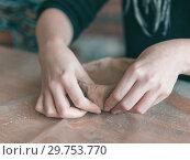 Купить «Ceramist hands make a plate of brown clay. retro. vintage», фото № 29753770, снято 19 января 2019 г. (c) Ольга Сергеева / Фотобанк Лори