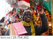 Купить «Guy choosing Christmas decorations», фото № 29754302, снято 8 декабря 2018 г. (c) Яков Филимонов / Фотобанк Лори