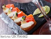 Купить «Canapes with salmon and black olives on cream sauce», фото № 29754662, снято 14 декабря 2019 г. (c) Яков Филимонов / Фотобанк Лори