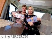 Купить «Cheerful middle age married positive travelers couple sitting inside of camper holds showing hippy retro styled number plate or license number with text This the season to be married and I love life», фото № 29755730, снято 11 ноября 2018 г. (c) Alexander Tihonovs / Фотобанк Лори