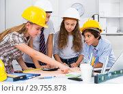 Купить «Teens engineers discussing draft at the table», фото № 29755878, снято 12 октября 2017 г. (c) Яков Филимонов / Фотобанк Лори