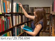 Молодая девушка выбирает книги в библиотеке. Стоковое фото, фотограф Иванов Алексей / Фотобанк Лори