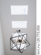 Купить «Skylight windows and black steel hexagonal lighting fixture with five clear glass bulbs hung above the staircase inside a modern cube style home, Quebec...», фото № 29773050, снято 29 июля 2016 г. (c) age Fotostock / Фотобанк Лори