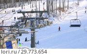 Купить «Chairlift in mountain ski resort in winter sunny day», видеоролик № 29773654, снято 23 января 2019 г. (c) FotograFF / Фотобанк Лори