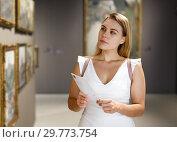 Купить «Woman visiting painting exhibition», фото № 29773754, снято 28 июля 2018 г. (c) Яков Филимонов / Фотобанк Лори
