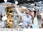 Купить «Smiling couple customers choosing floor lamp with a long standard in store», фото № 29778462, снято 29 января 2018 г. (c) Яков Филимонов / Фотобанк Лори
