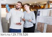 Купить «Glad couple looking sample of ceramic tile», фото № 29778526, снято 2 февраля 2018 г. (c) Яков Филимонов / Фотобанк Лори