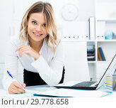 Купить «Mindful girl makes notes with pen in document on desk in well-lit office», фото № 29778658, снято 17 октября 2017 г. (c) Яков Филимонов / Фотобанк Лори
