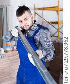Купить «Repairman is looking at the level of the profile», фото № 29778962, снято 3 июня 2017 г. (c) Яков Филимонов / Фотобанк Лори