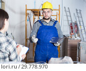 Купить «Male worker with spatula is clarifying details from client», фото № 29778970, снято 3 июня 2017 г. (c) Яков Филимонов / Фотобанк Лори