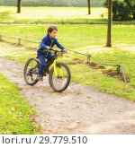 Little boy of 4 years in sports suit riding a bike along paths of the park. Стоковое фото, фотограф Юлия Бабкина / Фотобанк Лори