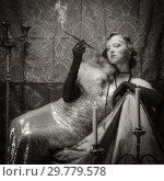 Купить «Girl in an evening dress with a cigarette mouthpiece. Studio portrait in retro style, toned in sepia», фото № 29779578, снято 27 декабря 2018 г. (c) Вадим Орлов / Фотобанк Лори