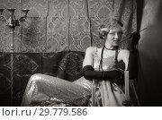 Купить «Girl in an evening dress with a cigarette mouthpiece. Studio portrait in retro style, toned in sepia», фото № 29779586, снято 27 декабря 2018 г. (c) Вадим Орлов / Фотобанк Лори