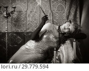 Купить «Girl in an evening dress with a cigarette mouthpiece. Studio portrait in retro style, toned in sepia», фото № 29779594, снято 27 декабря 2018 г. (c) Вадим Орлов / Фотобанк Лори