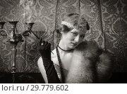 Купить «Girl in an evening dress with a cigarette mouthpiece. Studio portrait in retro style, toned in sepia», фото № 29779602, снято 27 декабря 2018 г. (c) Вадим Орлов / Фотобанк Лори