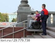 Купить «Охранник помогает инвалиду-колясочнику спускаться на лестничном подъемнике», фото № 29779738, снято 9 сентября 2018 г. (c) EgleKa / Фотобанк Лори