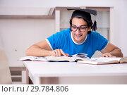 Купить «Young handsome student studying at home», фото № 29784806, снято 31 октября 2018 г. (c) Elnur / Фотобанк Лори