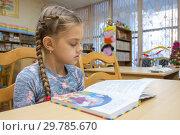 Купить «Девочка десяти лет читает книгу в библиотеке», фото № 29785670, снято 15 января 2019 г. (c) Иванов Алексей / Фотобанк Лори