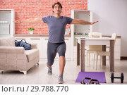 Купить «Young handsome man doing sport exercises at home», фото № 29788770, снято 12 сентября 2018 г. (c) Elnur / Фотобанк Лори