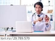Купить «Young handsome doctor cardiologist in front of whiteboard», фото № 29789570, снято 21 ноября 2018 г. (c) Elnur / Фотобанк Лори