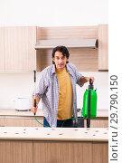Купить «Professional contractor doing pest control at kitchen», фото № 29790150, снято 29 октября 2018 г. (c) Elnur / Фотобанк Лори