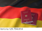 Passport of Germany on the flag of the Germany. Getting a Germnay passport, naturalization and immigration concept. Стоковое фото, фотограф Maksym Yemelyanov / Фотобанк Лори
