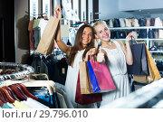 Купить «Two glad girls having many shopping bags», фото № 29796010, снято 27 июня 2019 г. (c) Яков Филимонов / Фотобанк Лори