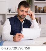 Купить «Sadly young man struggling to pay utility bills», фото № 29796158, снято 25 декабря 2017 г. (c) Яков Филимонов / Фотобанк Лори