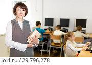 Купить «Friendly female teacher in computer class», фото № 29796278, снято 19 декабря 2018 г. (c) Яков Филимонов / Фотобанк Лори